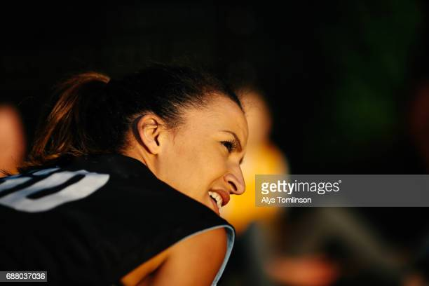 young woman in netball bib leaning over and smiling