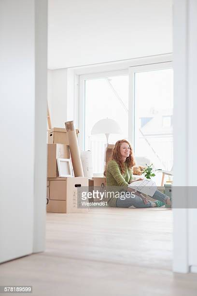 Young woman in new flat with cardboard boxes looking at ground plan