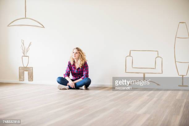 Young woman in new home sitting on floor thinking about interior design