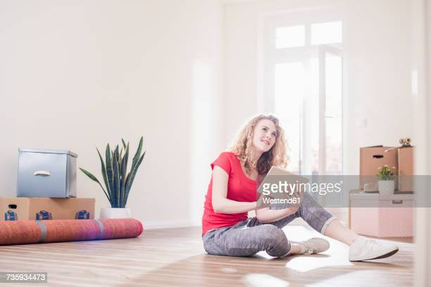 Young woman in new home sitting on floor with tablet