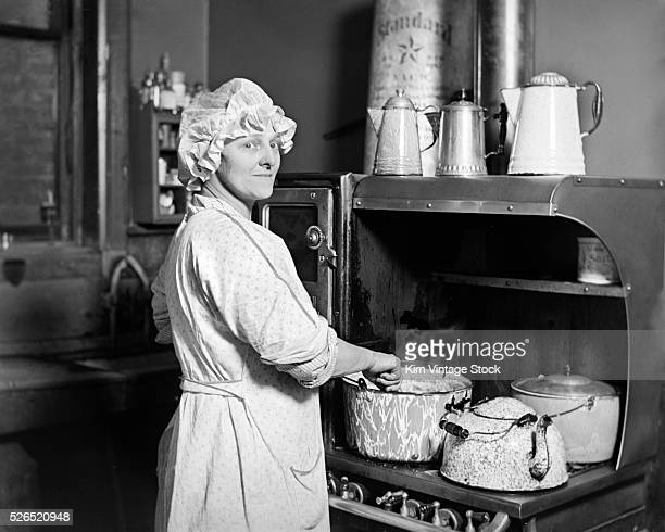 Young woman in night clothes and night cap stands at a period stove happily stirring away.
