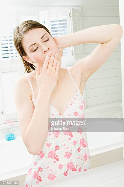 Young woman in nightgown yawning in front of bathroom mirror