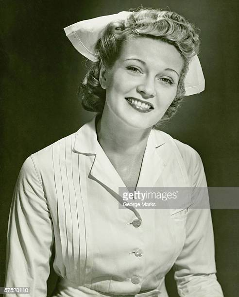 young woman in nurse clothing smiling, (b&w) - 20th century stock photos and pictures