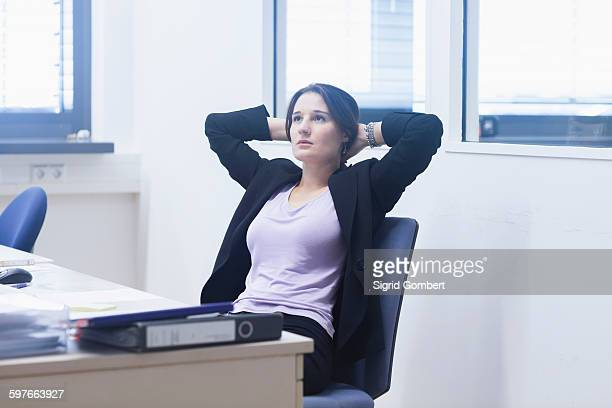 young woman in office leaning back in chair hands behind head looking away - sigrid gombert stock pictures, royalty-free photos & images