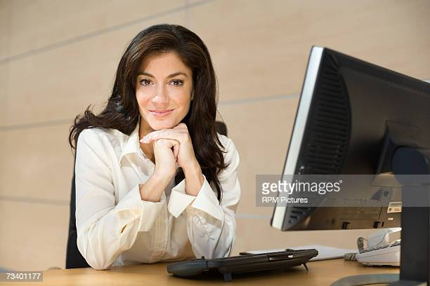 Young woman in office leaning chin on hands, portrait