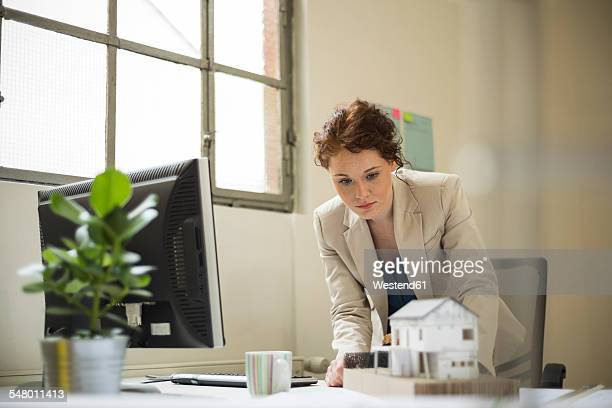 Young woman in office looking at architectural model