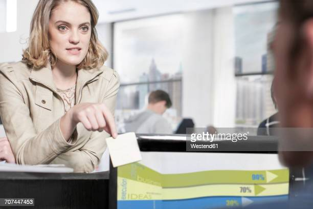 young woman in office looking at colleague - work romance stock pictures, royalty-free photos & images