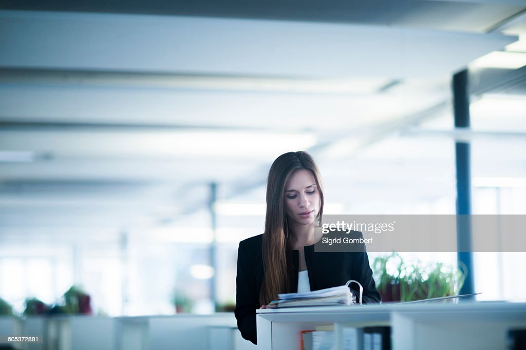 Young woman in office looking down at paperwork in ringbinder file : Stock-Foto