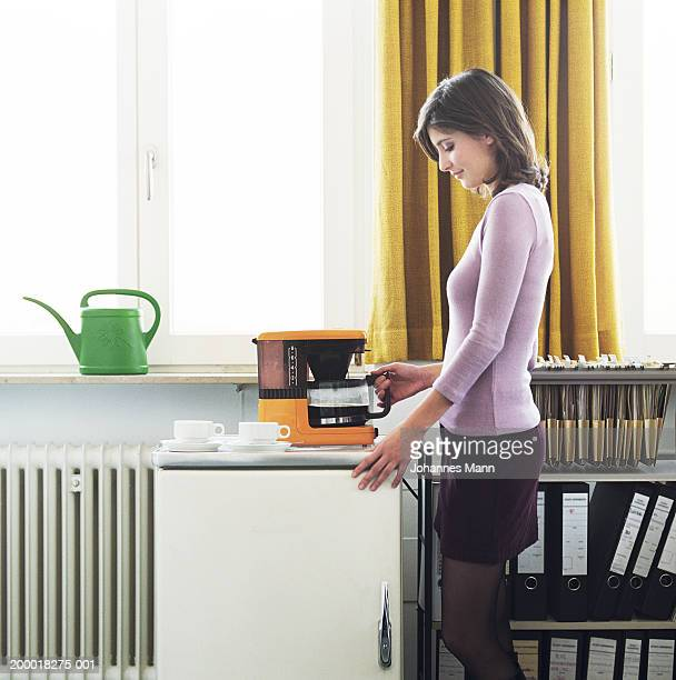 Young woman in office preparing coffee