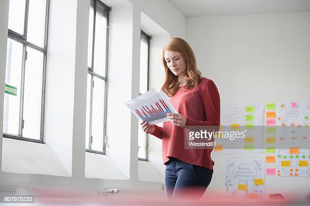 Young woman in office reading charts