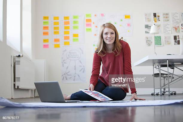 young woman in office sitting on floor working through papers - abbigliamento elegante foto e immagini stock