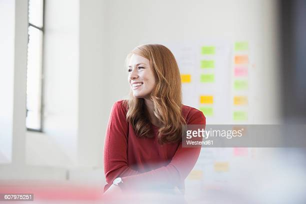 Young woman in office smiling happily