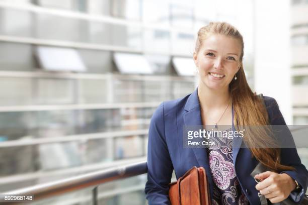Young woman in office stood against window