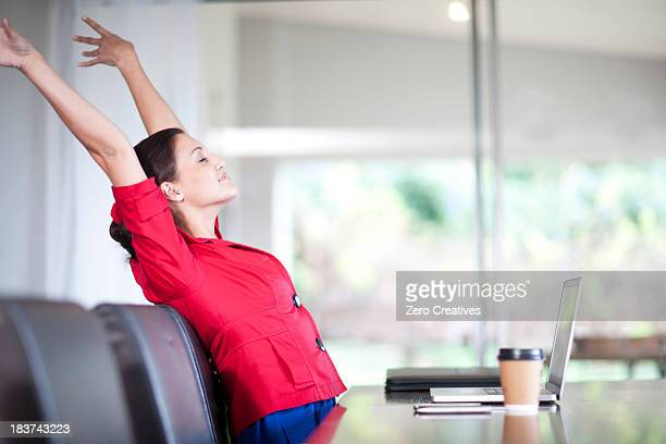 Young woman in office stretching
