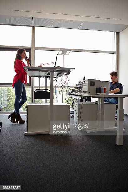 Young woman in office telephoning at adjustable desk
