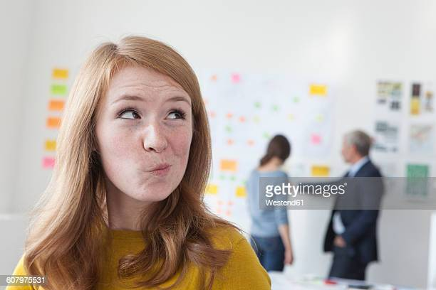 Young woman in office thinking