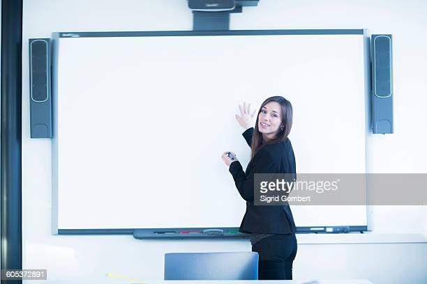 young woman in office using whiteboard, looking over shoulder at camera smiling - sigrid gombert stockfoto's en -beelden