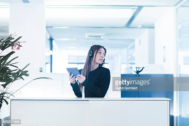 Young woman in office wearing telephone headset, holding digital tablet looking away over shoulder
