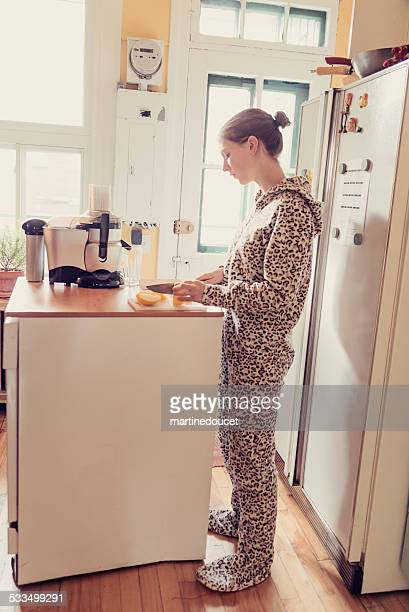 """young woman in onesie using a juicer in small kitchen. - """"martine doucet"""" or martinedoucet stock pictures, royalty-free photos & images"""