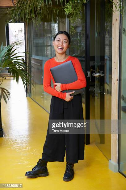 young woman in open plan office holding laptop - ビジネスウェア ストックフォトと画像