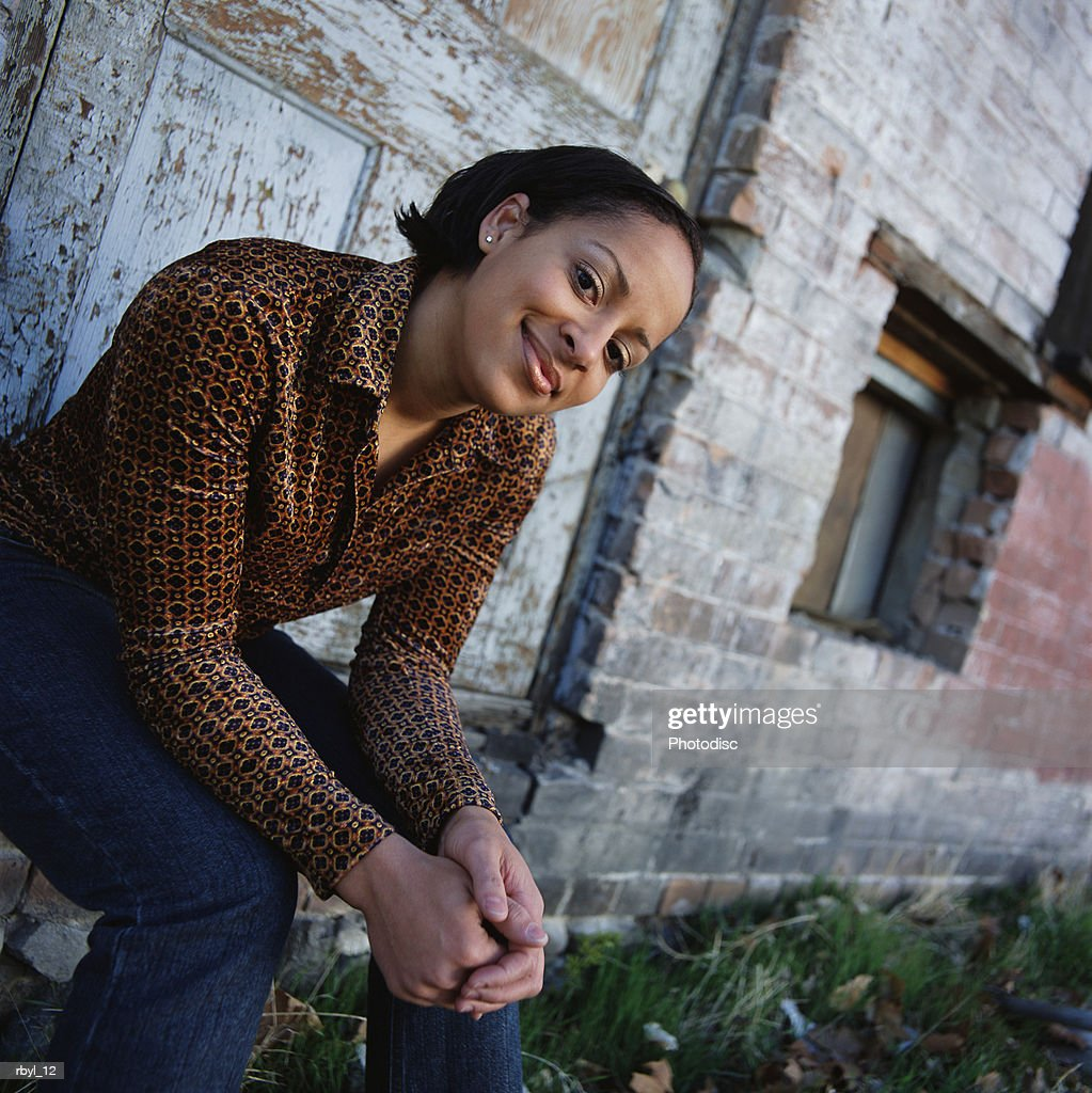 young woman in orange long sleeve shirt blue jeans sits on the doorstep of old abandoned building : Foto de stock
