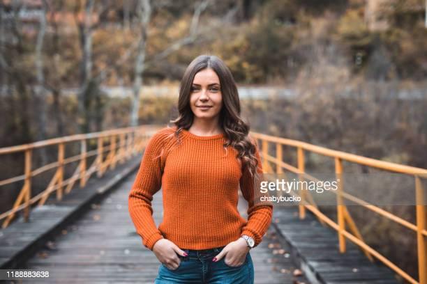 橋の上にオレンジ色のセーターを着た若い女性 - オレンジ色のシャツ ストックフォトと画像