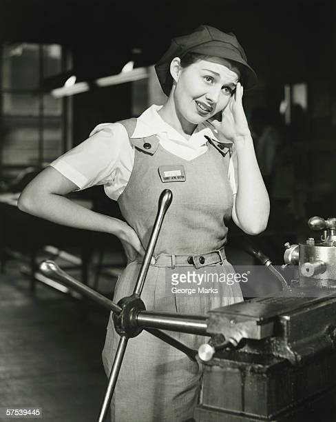 Young woman in overalls standing by lathe in factory, (B&W)