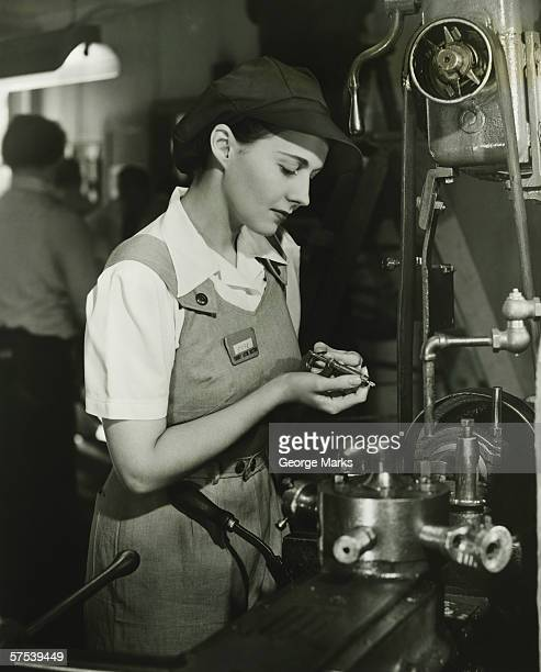 Young woman in overalls working by lathe in factory, (B&W)