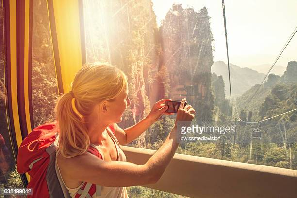 Young woman in overhead cable car taking smart phone picture