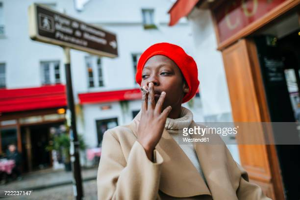 young woman in paris smoking a cigarette - femme qui fume photos et images de collection