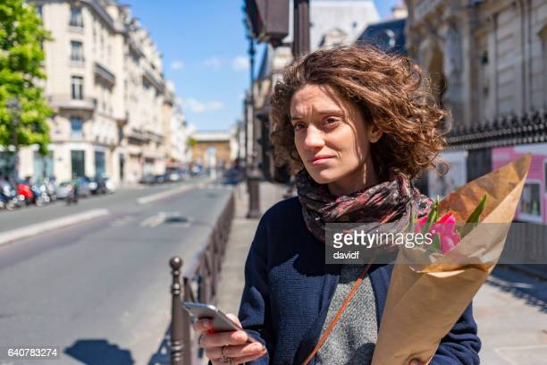 young woman in paris with a phone for ride sharing transport - french women stock photos and pictures