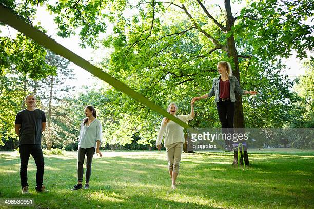Jeune femme dans le parc, en équilibre sur une slackline