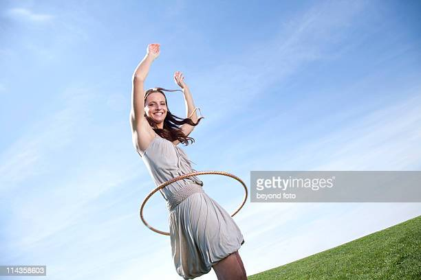 young woman in park doing hula hoop
