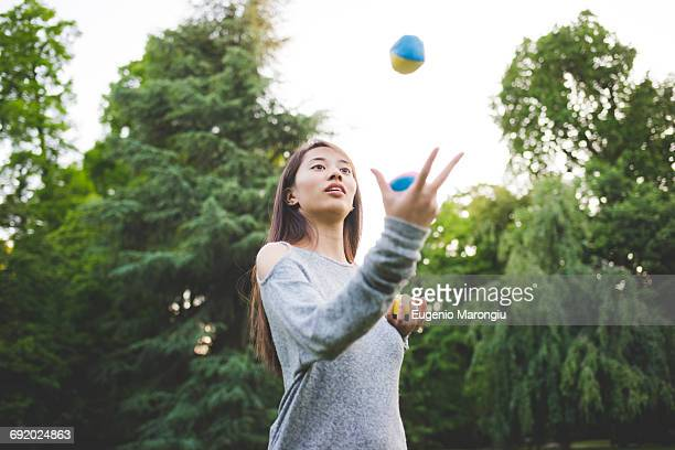 Young woman in park juggling balls