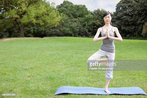 young woman in park practicing yoga tree pose - tree position stock photos and pictures