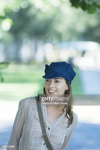 young woman in park, wearing cap, looking out of frame - out of frame stock pictures, royalty-free photos & images