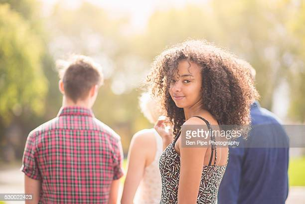 young woman in park with friends looking over her shoulder - bethnal green stock pictures, royalty-free photos & images