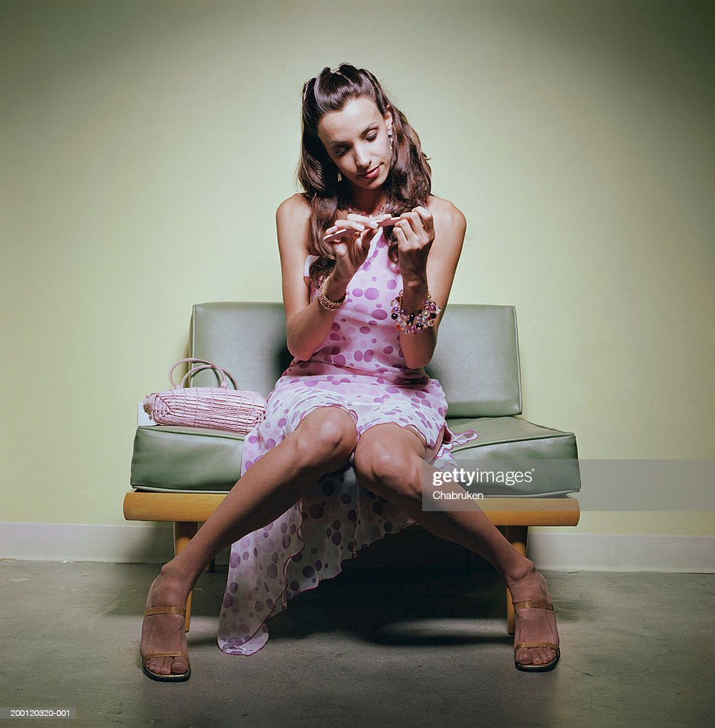 Young woman in party dress sitting on sofa filing nails : Stock Photo