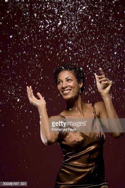 Young woman in party dress tossing confetti
