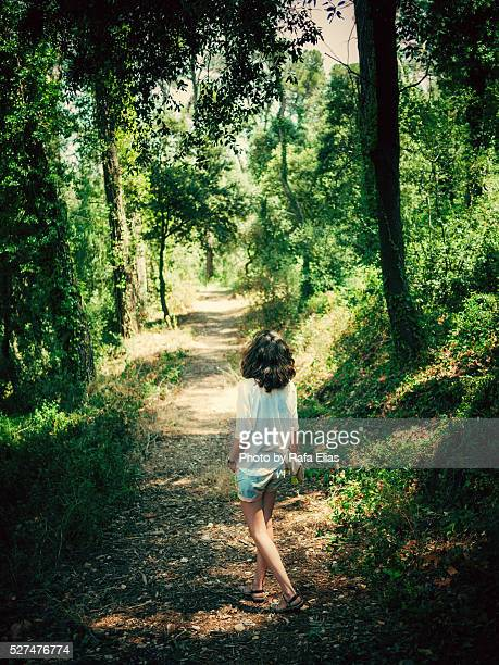 Young woman in path at forest
