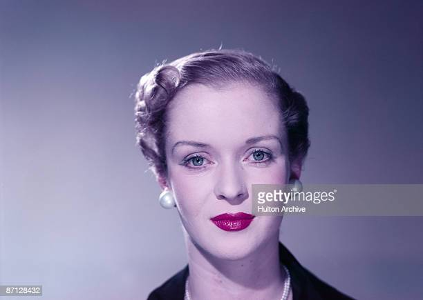 A young woman in pearl earrings and pink lipstick circa 1950