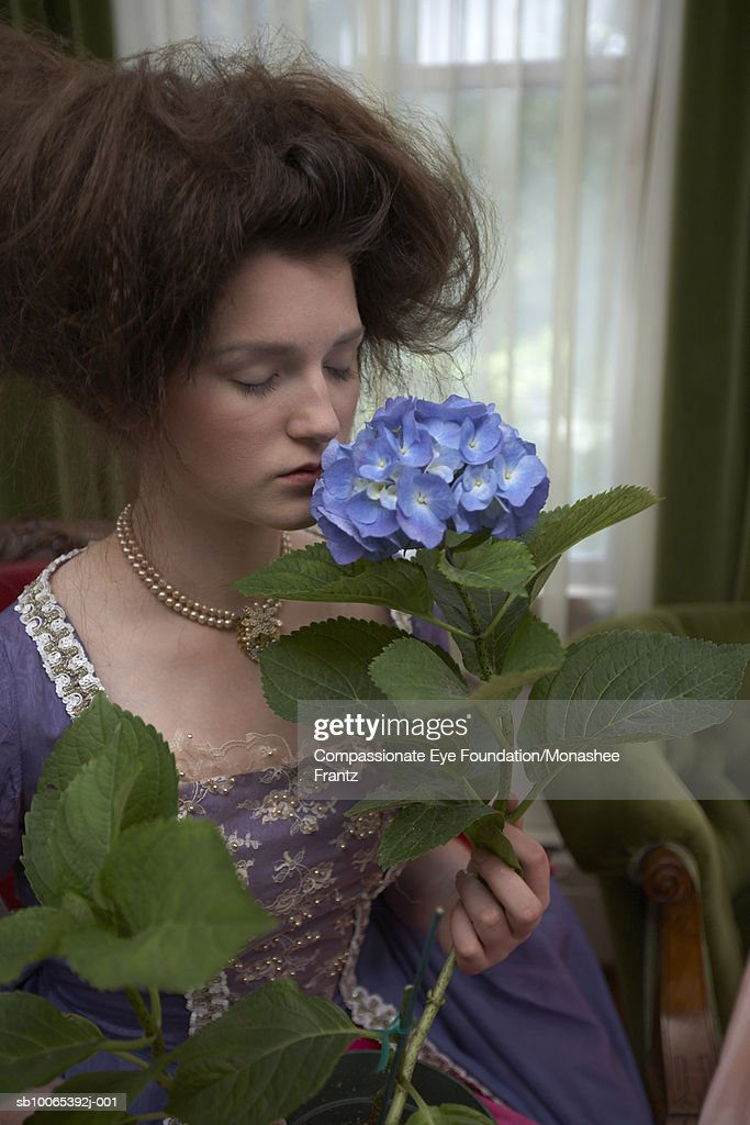 Young woman in period dress smelling flower : Foto stock