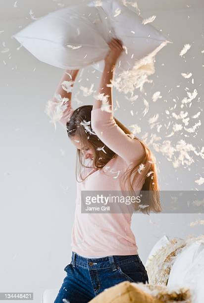 Young woman in pillow fight