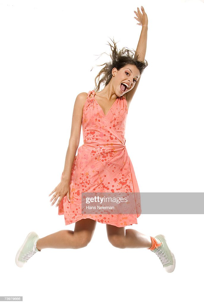 Young woman in pink dress and white tennis shoes jumping into air : Stock Photo