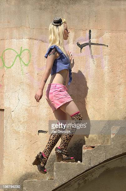 young woman in pink hot pants climbing staircase - depczyk stock pictures, royalty-free photos & images