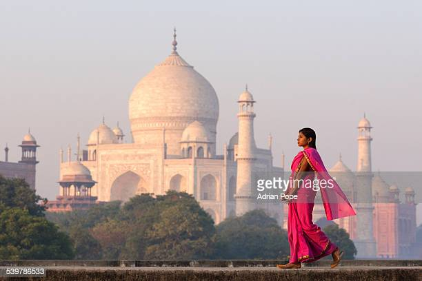 Young woman in pink sari with Taj Mahal in distanc