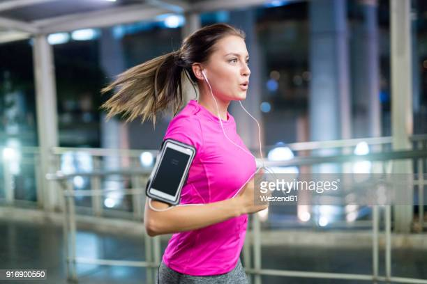 young woman in pink sportshirt running in city at night - jogging stock pictures, royalty-free photos & images