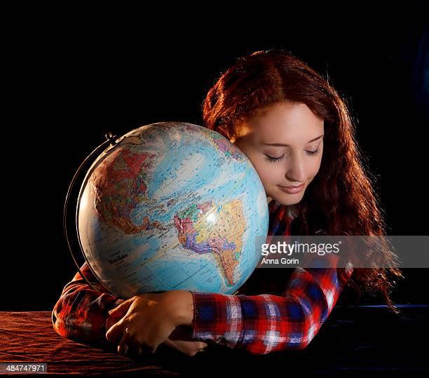 Young woman in plaid shirt hugs globe