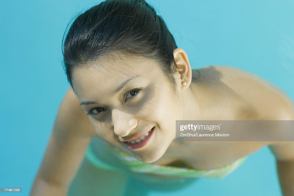 Young Woman In Pool Wearing Bikini Looking Up At Camera Closeup High