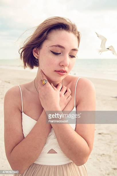 "young woman in prom dress on the beach with  bird. - ""martine doucet"" or martinedoucet stock pictures, royalty-free photos & images"